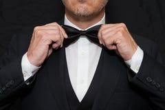 O cavalheiro no traje de cerimônia endireita seu Bowtie Foto de Stock Royalty Free