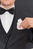 O cavalheiro no traje de cerimônia fixa o quadrado do bolso, vertical Imagens de Stock Royalty Free