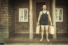 O cavalheiro vestiu em 1920 o roupa de banho da era dos 's que guarda malas de viagem sobre Fotos de Stock Royalty Free