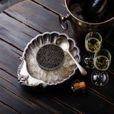 O caviar preto pode dentro no gelo na bacia e no champanhe de prata fotos de stock