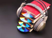 O CD cola para fora dos livros vermelhos com os fones de ouvido nele Fotos de Stock Royalty Free