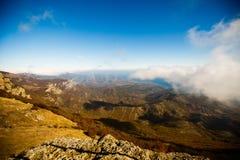 O cenário do outono de cumes e de montes amarelos e alaranjados da montanha fotografou da cimeira acima das nuvens dramático Foto de Stock Royalty Free