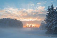 O cenário nevado da manhã do inverno com luz solar do alvorecer irradia a quebra Imagens de Stock Royalty Free