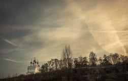 O cenário rural dramático do campo com a igreja no monte e o céu dramático do por do sol copiam o espaço imagem de stock royalty free