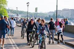 O Central Park de Gorky da cultura e do lazer completamente dos locals, povos monta bicicletas na terraplenagem ao longo do rio d fotografia de stock