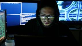 O centro da segurança do Cyber encheu-se com as telas de exposição, hacker masculino que trabalha no computador, programador prof filme