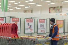 O centro de compra, um trabalhador limpa os carros para produtos, editoriais imagem de stock royalty free