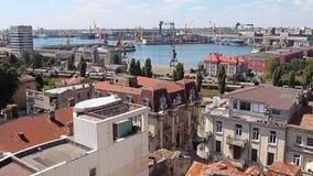 O centro histórico velho de Constanta, em Romênia, com uma mistura de construções antigas e modernas com o porto comercial atrás vídeos de arquivo