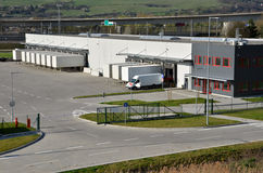 O centro moderno da logística, a camionete branca e o standingon dos reboques ramp Imagem de Stock Royalty Free