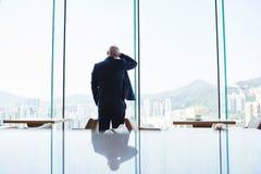 O CEO do homem é janela próxima ereta do escritório com vista da cidade de Hong Kong imagem de stock royalty free