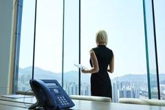 O CEO orgulhoso da mulher com a tabuleta digital nas mãos pensativas está olhando na janela do escritório Fotografia de Stock