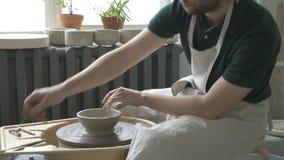 O ceramist novo está trabalhando na máquina de giro na oficina da cerâmica vídeos de arquivo