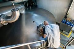 O cervejeiro do especialista controla o processo de fermentação da cerveja fotos de stock royalty free