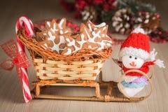 O cesta-trenó do presente com cookies, doces e um boneco de neve do brinquedo vestiu-se na roupa Imagem de Stock