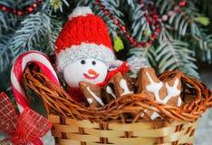 O cesta-trenó do presente com cookies, doces e um boneco de neve do brinquedo vestiu-se na roupa morna Imagem de Stock