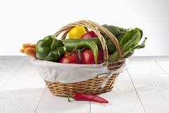 O cesto de compras encheu-se com os vários vegetais orgânicos frescos no fundo de madeira branco Imagem de Stock Royalty Free