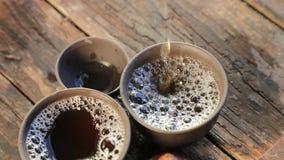 O chá é derramado lentamente em copos de chá especiais para o chá chinês filme