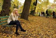 O chá bebendo da mulher no parque no outono Imagens de Stock