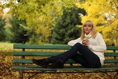 O chá bebendo da mulher no parque no outono Imagem de Stock Royalty Free