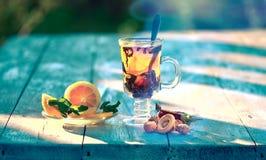 O chá com limão e a hortelã em uma caneca de vidro em um lwooden surgem Foto de Stock Royalty Free