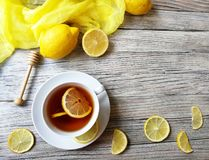 O chá com limão em um copo branco em um branco afligiu o fundo Imagens de Stock