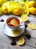 O chá com limão em um copo branco em um branco afligiu o fundo Foto de Stock Royalty Free
