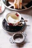 O chá de camomila quente serviu no copo do vintage da porcelana com infuser de aço inoxidável do filtro do chá na tabela superior imagens de stock royalty free