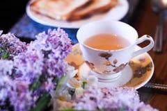 O chá de Masala chai de india com pão, a manteiga e o lilás florescem Fotografia de Stock