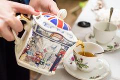 O chá derramou no copo de chá com símbolos britânicos Imagens de Stock Royalty Free
