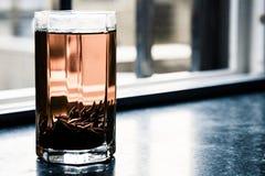 O chá do puerh de Shu fabricou cerveja no copo de vidro no peitoril da janela Fotos de Stock Royalty Free
