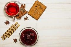 O chá em um copo com doce de framboesa, cookies, croissant, canela, anis, caramelo cola Em uma tabela de madeira branca Composit  fotografia de stock royalty free