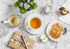 O chá, panqueca, molho de maçã, presente caseiro no papel de embalagem, floresce a violeta em um fundo claro Tabela de café da ma Fotos de Stock Royalty Free