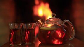 O chá quente com dois vidros aproxima a chaminé Conceito acolhedor mágico da noite Copie o espaço vídeos de arquivo