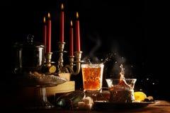 O chá quente com respingo e vapor, as velas e os doces fazem a obscuridade Fotos de Stock