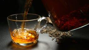 O chá quente derrama a um copo de um bule imagem de stock royalty free