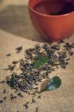 O chá seco com verde sae no copo, no fundo de serapilheira Fotos de Stock Royalty Free