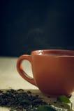 O chá seco com verde sae no copo, no fundo de serapilheira Imagens de Stock Royalty Free