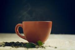 O chá seco com verde sae no copo, no fundo de serapilheira Imagem de Stock Royalty Free