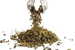 O chá verde chinês do teguanin, dispersado em um fundo branco, derramou com uma espátula do chá e um filtro do chá fotos de stock