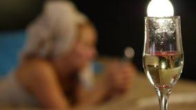 O champanhe do close-up flui em um vidro A moça bonita que descansa confortavelmente em uma cama e lê um livro Movimento lento video estoque