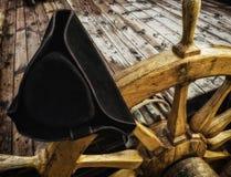 O chapéu armado no volante de madeira velho do navio foto de stock