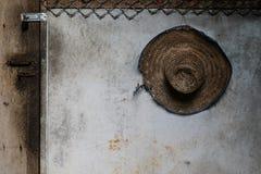 O chapéu de palha usado do fazendeiro pendurou em uma parede imagens de stock royalty free