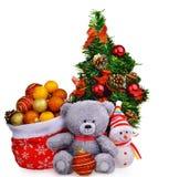 O chapéu de Santa Claus e a árvore de Natal com o urso de peluche macio das quinquilharias brincam o homem da neve Imagem de Stock Royalty Free