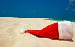 O chapéu de Santa está em uma praia Imagens de Stock