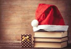 O chapéu de Santa sobre livros aproxima a caixa de presente Imagem de Stock Royalty Free