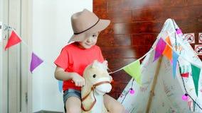 O chapéu de vaqueiro vestindo do menino feliz pequeno está montando um cavalo do brinquedo na sala de jogos foto de stock