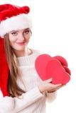O chapéu do ajudante de Santa da menina guarda caixas de presente dadas forma coração Fotos de Stock Royalty Free