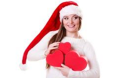 O chapéu do ajudante de Santa da menina guarda caixas de presente dadas forma coração Fotos de Stock
