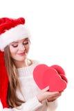 O chapéu do ajudante de Santa da menina guarda caixas de presente dadas forma coração Imagens de Stock Royalty Free