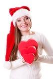 O chapéu do ajudante de Santa da menina guarda caixas de presente dadas forma coração Fotografia de Stock